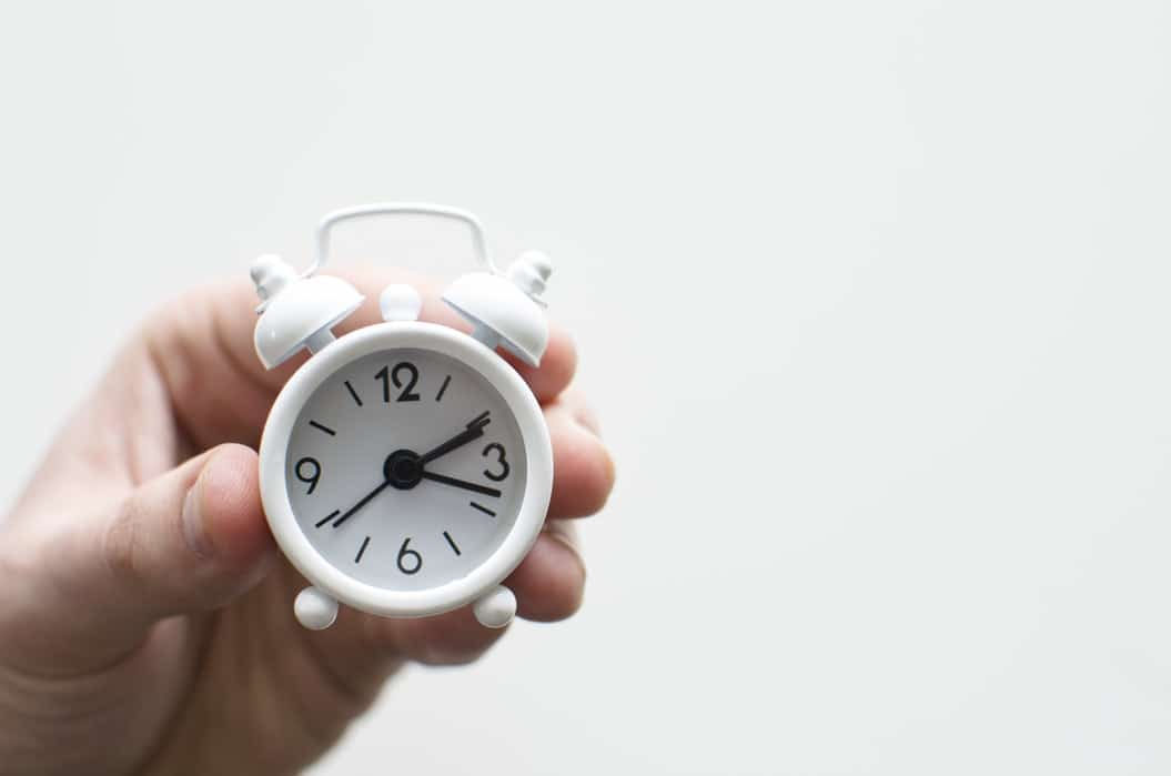 Gagner du temps - bob desk logiciel maintenance préventive- petit réveil matin dans la main d'un humain, sur fond blanc