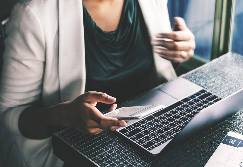 Gagner du temps - bob desk logiciel maintenance préventive- femme qui travaille devant un macbook et tenant un téléphone portable