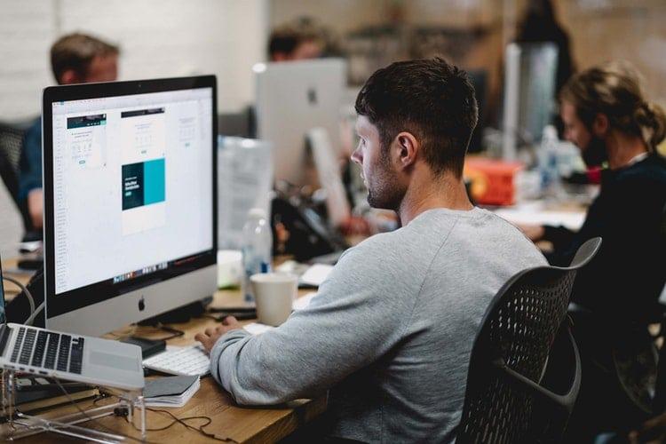 Facteurs clés de productivité en entreprise : outil de gmao maintenance : un homme envoie des mails sur son laptop