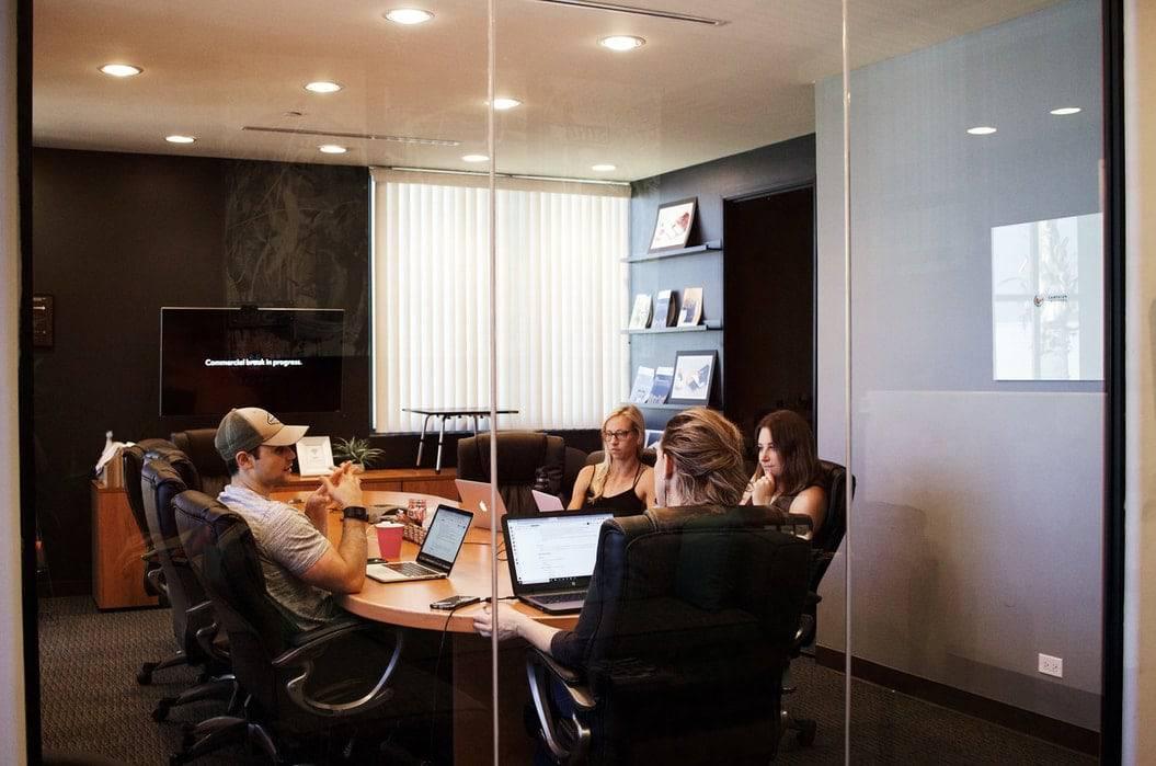 Bob! desk - logiciel de maintenance - qu'est ce qu'un office manager - table de collègues réunis dans une salle de réunion