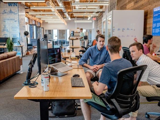 Employé du mois - Coworkers/collègues assis à une table dans un openspace - Employé du mois : la reconnaissance au travail ? - Bob! Desk, logiciel de maintenance, GMAO, logiciel SAAS